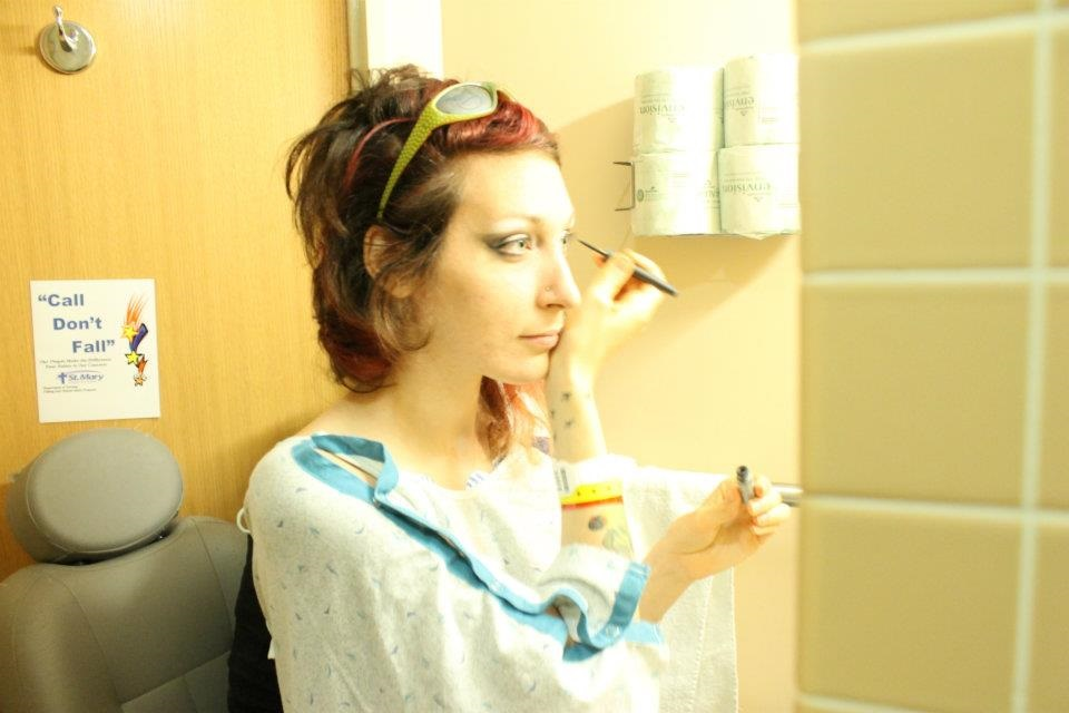 Anomie Fatale puts on makeup in a hospital bathroom