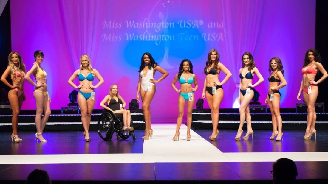 Kyann is sitting in her chair with her right hand on her right hip. She is in a line of eight girls--fourth from the left. All other girls are standing with their right hand on their right hip.