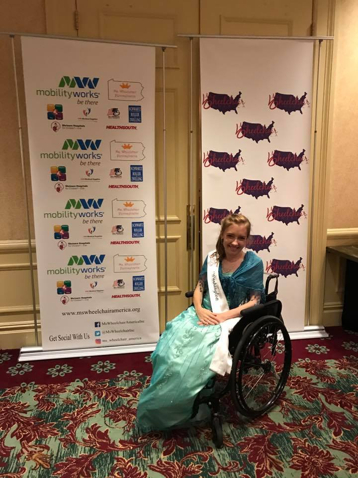 Kyann is sitting in her chair with her hands folded on her lap. She is sitting in front of the Ms. Wheelchair America sign.