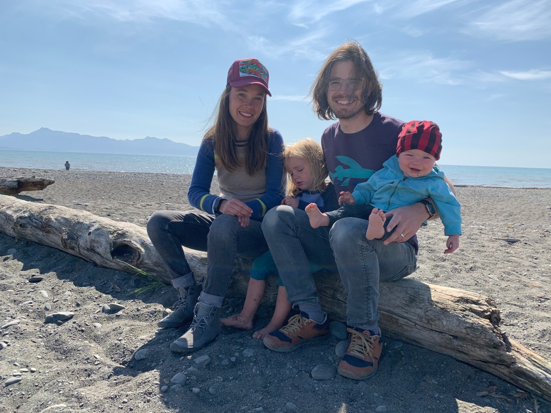Alex with her husband and two children, sitting on a deadwood log at the beach
